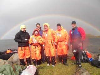 The group pose for a photo under a rainbow after a bracing swim!